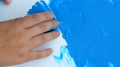 Blue paint covering white paper Stock Footage