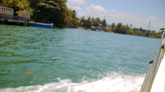 View from boat making waves travel on Kalu Ganga river in Sri Lanka Stock Footage
