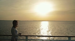 Silhouette of woman on deck of cruise ship at sunrise Stock Footage