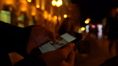 Closeup of young man hands scrolling internet on phone. Night illuminated city Stock Footage