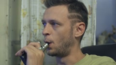 The young man sits at a table and smokes an electronic cigarette, lets couples Stock Footage