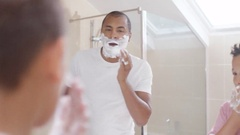 4K Father & son in bathroom in the morning, little boy copies his father shaving Stock Footage