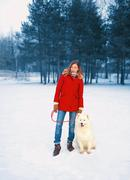 Pretty young woman with white Samoyed dog together on snow in winter day, wal Stock Photos