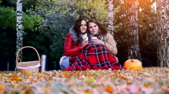 Young women sitting on picnic bundled up in a blanket drinking hot tea from Stock Footage