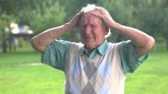Senior man holds his head. Stock Footage