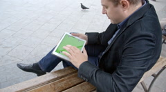 Man Wearing Suit Working With Tablet On A Bench, Greenscreen Stock Footage