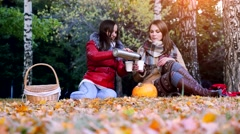 Young brunette women sitting on picnic bundled up in a blanket drinking hot tea Stock Footage