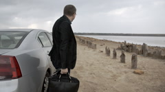 Man With Bag Walking Near Car In The Countryside In Slowmotion Stock Footage