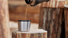 Builder makes coffee break from a thermos. Wooden buildings in the background Stock Footage