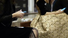 Two young female models in a beautiful dress couture uses the phone on the Stock Footage