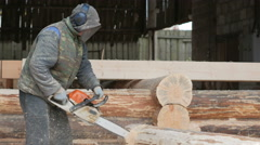Man cuts wood chainsaw for future home. Protective face mask on the face of the Stock Footage
