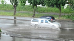 Cars driving through road flooded with water Stock Footage