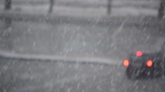 Snow falling on blurred road with moving cars Stock Footage
