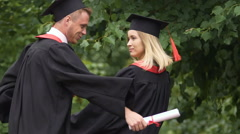 Happy pair of graduate students dancing and fooling around, holding diplomas Stock Footage