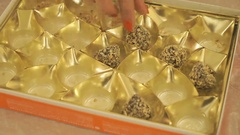 Woman's hand taking a chocolate truffle from a box Stock Footage