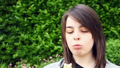 Young adult woman in park eating cereral bar Stock Footage
