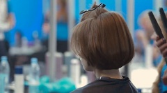 Female model whith basic bob getting hair straightened by hairdresser closeup on Stock Footage
