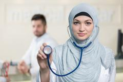 Front view of an arab doctor woman showing stethoscope. Stock Photos