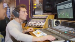 4K Professional team in recording studio mixing a track with male vocalist Stock Footage