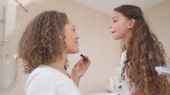 4K Little girl watching her mother in bathroom and playing with her make-up Stock Footage