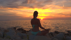 CLOSE UP: Beautiful woman in lotus yoga position by the ocean on magical evening Stock Footage