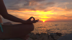 CLOSE UP: Muscular woman on rocky ocean beach in lotus yoga position at sunset Stock Footage