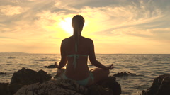 CLOSE UP: Tranquil girl in yoga pose on rocky ocean shore at stunning sunset Stock Footage