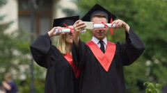Graduate students in academic dresses taking selfies after graduation ceremony Stock Footage