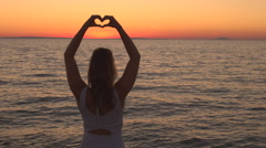 AERIAL, CLOSE UP: Girl looking at rippling sea and making heart shaped sign Stock Footage