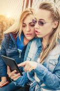 Two girlfriends having fun with digital tablet Stock Photos