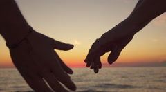 SLOW MOTION, CLOSE UP: Loving boy and playful woman handholding at ocean beach Stock Footage