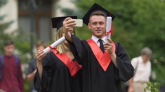 Man and woman in academic dresses taking selfie after graduation ceremony Stock Footage