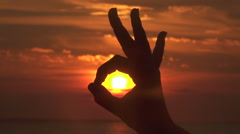 CLOSE UP, DOF: Making an okay gesture over fiery sky and capturing golden sun Stock Footage