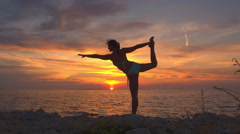 CLOSE UP: Flexible young woman doing yoga king dancer pose on rocky ocean shore Stock Footage