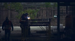 Welder weld metal beams at a construction site at night Stock Footage