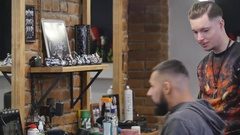 Hairdresser sweeps odds and ends with brush off back of the head of handsome Stock Footage