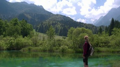 Jib shot - Young caucasian female standing at Zelenci Springs Stock Footage