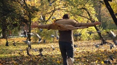 Man chasing pigeons in autumn park 240fps  Stock Footage