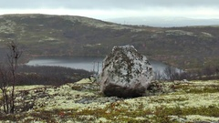 A big stone on the background of the lake in the mountain tundra. Stock Footage