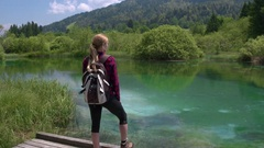 Tracking shot - Female standing at Zelenci Springs looking at the natural beauty Stock Footage