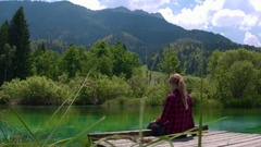 Full shot - Young caucasian female sittin on wooden pier at Zelenci Springs Stock Footage