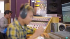 4K Music producer in recording studio mixing a track with female vocalist Stock Footage