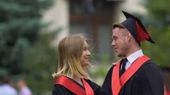 Smiling couple talking at graduation party, man throwing cap into air, happiness Stock Footage