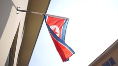 North Korea national flag flying in sky Stock Footage