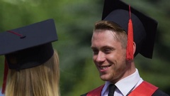 Couple of beautiful graduates smiling and hugging, enjoying moment, emotions Stock Footage