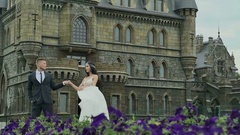 Happy beautiful bride and groom walking near the castle Stock Footage
