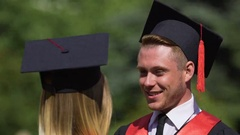 Caring male graduate adjusting tassels on girlfriend's cap, couple in love Stock Footage