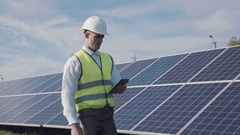 Technician walks beside array of solar panels Stock Footage