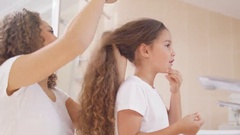 4K Mother styling her young daughter's hair in the bathroom in the morning Stock Footage