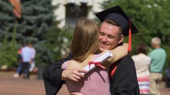 Young woman congratulating and hugging her graduate boyfriend, happy moments Stock Footage